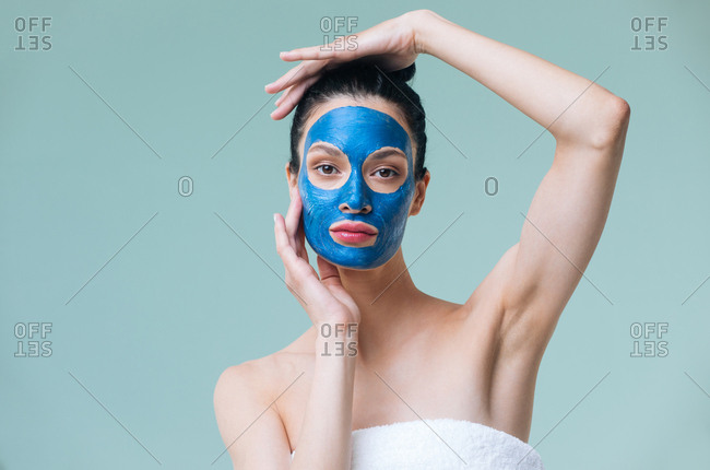 Studio portrait of attractive Caucasian woman model posing with blue clay mask on her face and looking at camera.