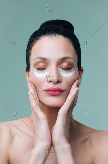 Studio portrait of beautiful Caucasian woman model posing with cosmetic mask under her eyes.