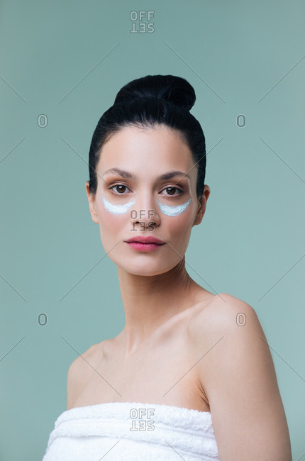 Studio portrait of beautiful Caucasian woman with cosmetic mask under her eyes and looking at camera.
