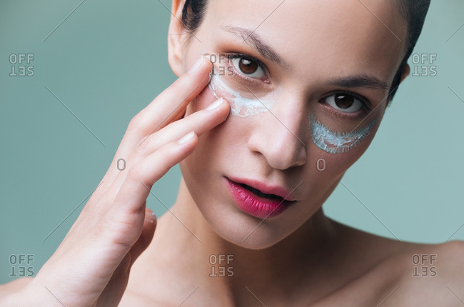 Close up of beautiful Caucasian woman putting cosmetic cream on her face and looking at camera.