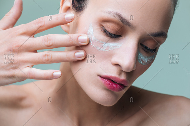 Close up of beautiful serious Caucasian woman putting cosmetic cream on her face.