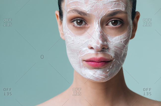 Beautiful Caucasian woman with cosmetic scrub cream on her face looking at camera.
