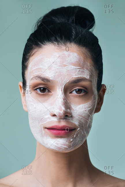 Beautiful Caucasian woman with cosmetic scrub cream on her face and looking at camera.