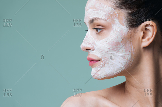 Beauty portrait of beautiful Caucasian woman posing with white cosmetic scrub cream on her face.