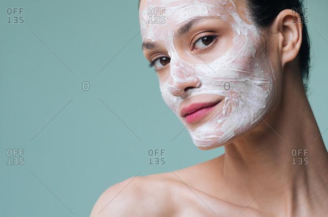 Beautiful Caucasian woman model posing with cosmetic scrub cream on her face.