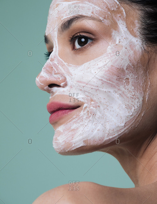 Portrait of beautiful Caucasian woman model posing with cosmetic scrub cream on her face.