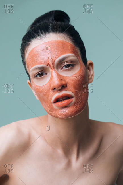 Beauty portrait of woman model posing with orange clay face mask on her face and looking at camera.