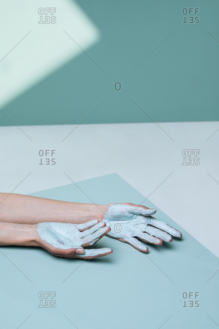 Studio photo of hands of unrecognisable woman and cosmetic clay mask on her palms.