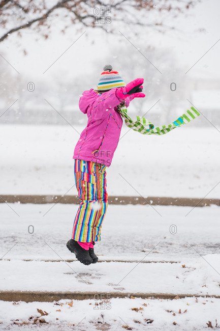 Little girl jumping in the snow