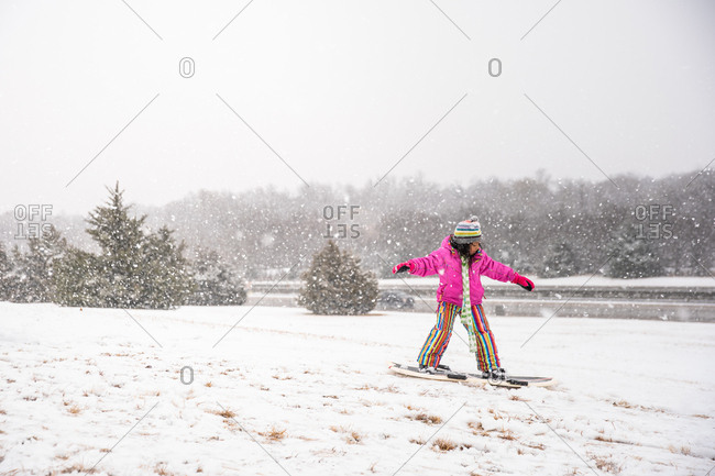 Little girl riding on a snowboard