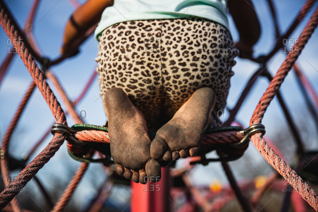Dirty feet of a little girl climbing on playground equipment