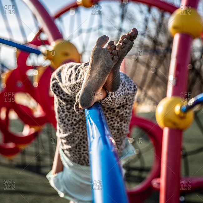Child climbing on playground equipment with dirty bare feet