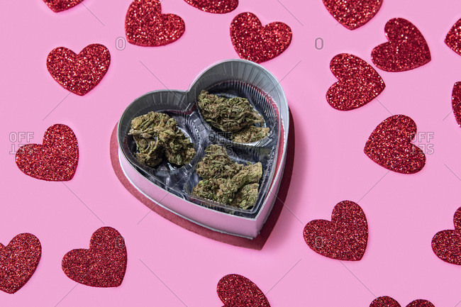 Red glitter hearts scattered around Valentine's Day candy box filled with marijuana on a pink background.