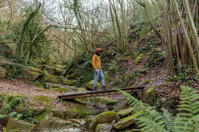 Side view of man walking on small wooden bridge over small creek while travelling through wet forest in Spain