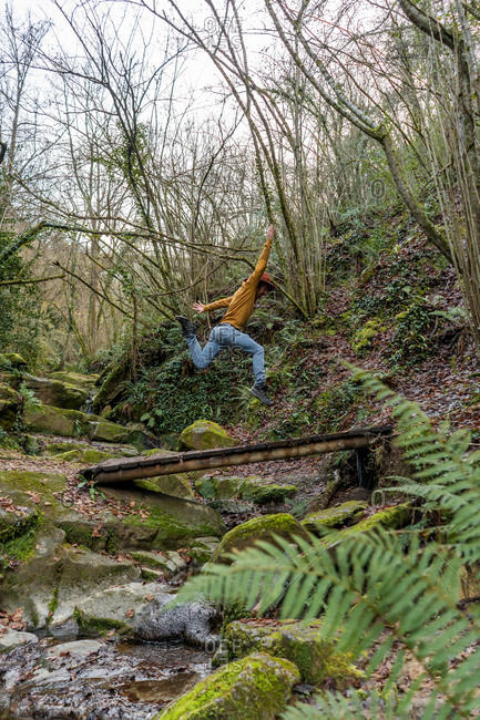 Side view of young guy in casual outfit jumping over creek with fresh water in beautiful forest in Spain