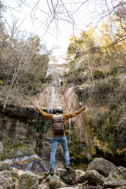 Back view of male traveler with outstretched arms standing on stones and admiring fantastic waterfall in forest in Spain