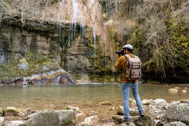 Back view of adult man with backpack using professional camera to take photos of calm river and rough cliff in amazing Spanish countryside
