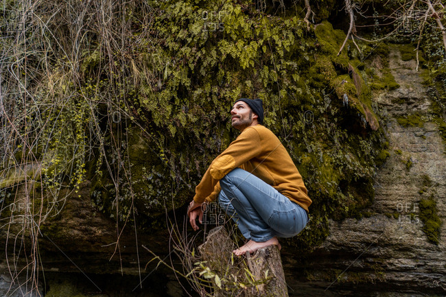 Side view of handsome barefoot male in casual outfit looking away while sitting on old stump in beautiful forest in Spain