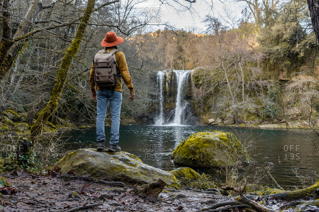 Back view of man with backpack stretching out arms and admiring beautiful waterfall while standing on boulder near forest lake in Spain