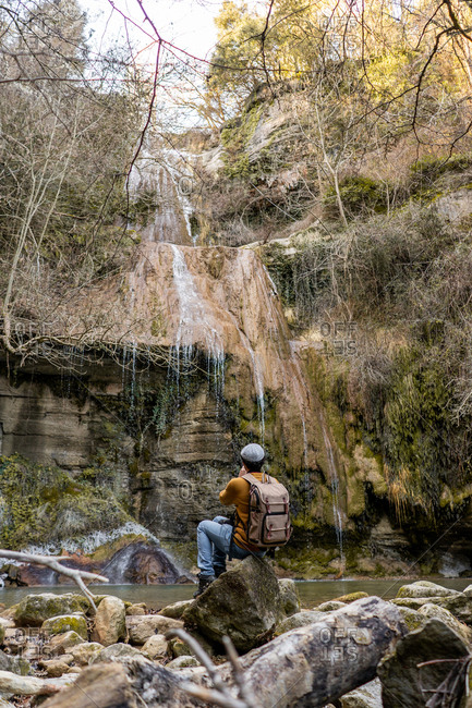 Back view of male traveler with sitting on stones and taking pictures with camera of fantastic waterfall in forest in Spain