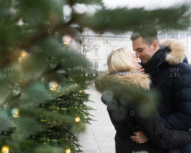 Side view of happy guy hugging young lady in ski jackets near Christmas tree decorated by illuminated fairy lights on city street