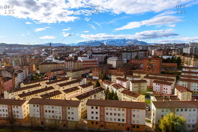 Panoramic view of town near high mountains and blue sky with clouds in sunny day