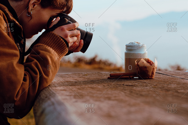 Side view of young female in casual outfit using professional camera to take picture of aromatic coffee and delicious muffin while sitting at timber table in countryside