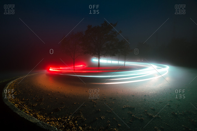 Abstract view of bright lines of lights on route between trees and mist in evening in countryside