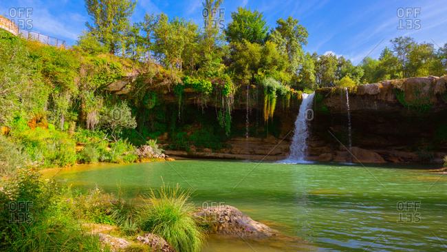 Beautiful view of fantastic Cascada de Pedrosa de Tobalina falling into calm lake on sunny day in Spain