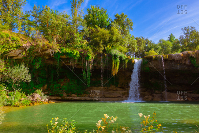 Beautiful view of fantastic Cascada de Pedrosa de Tobalina falling into calm lake on sunny day in Spain