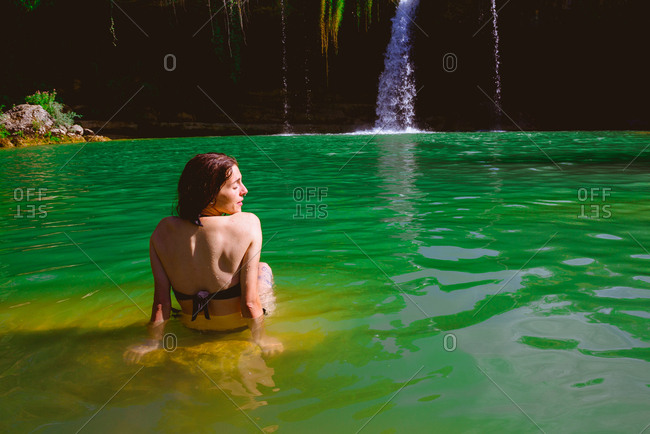 Back view of young lady in swimwear sitting and looking at majestic Cascada de Pedrosa de Tobalina while standing in calm lake on sunny day in Spain