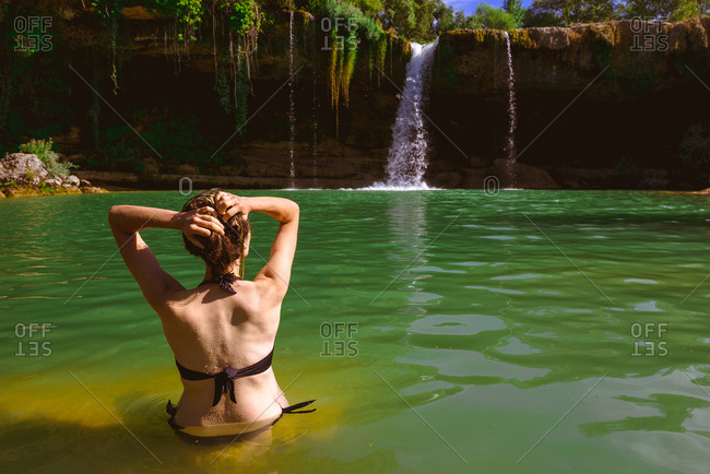 Back view of young lady in swimwear touching wet hair and looking at majestic Cascada de Pedrosa de Tobalina while standing in calm lake on sunny day in Spain