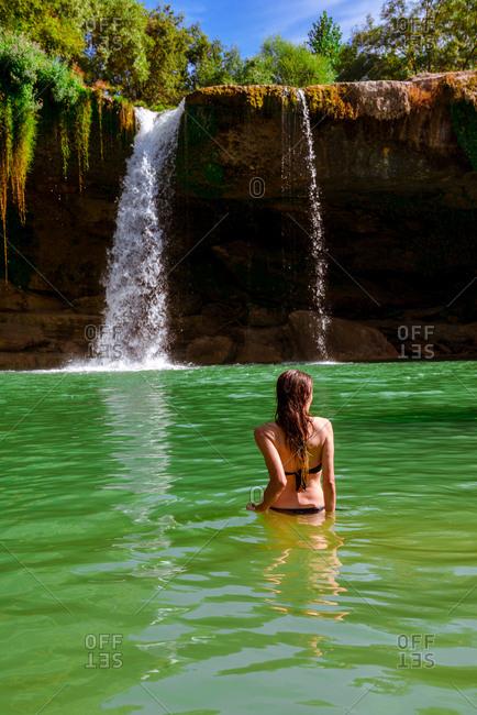 Back view of slim female in swimwear standing in clean water near fantastic Cascada de Pedrosa de Tobalina on sunny day