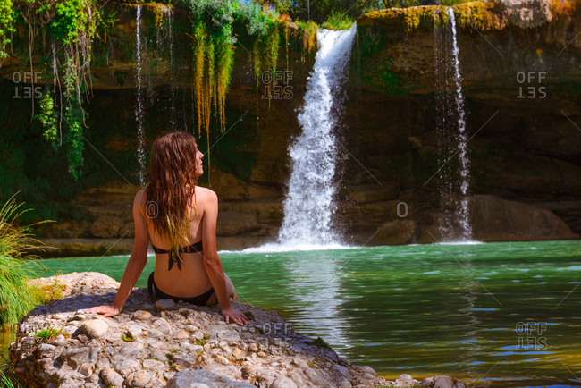 Back view of young woman in swimwear sitting on stone near calm lake and magnificent waterfall on sunny day in Spain