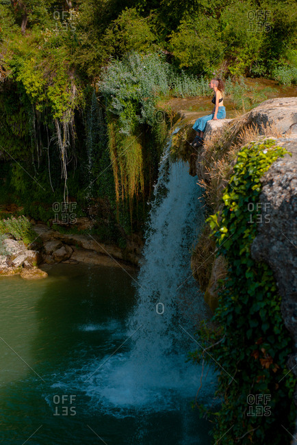 Side view of young female sitting on cliff near waterfall with fresh water on sunny day in Spanish countryside