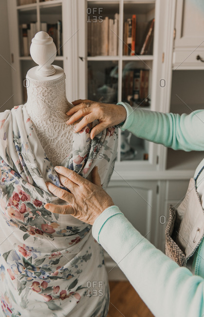 Unrecognizable senior female adjusting beautiful ornamental garment on dummy while working in cozy workshop
