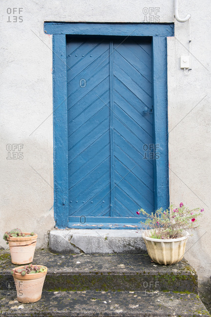 White construction with blue door and blooms in pots on stairs in Pyrenees