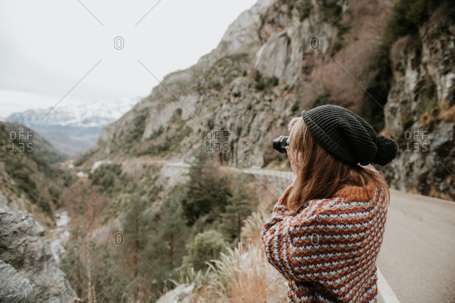 Side view of young lady in sweater and hat taking photo on camera between hills in Pyrenees