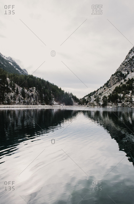 Amazing view of water surface between high mountains with trees in snow and cloudy heaven in Pyrenees