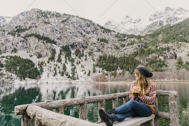 Young lady sitting on bench and looking away near amazing view of water surface between high mountains with trees in snow in Pyrenees