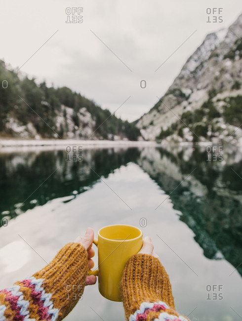 Crop hand of human holding yellow mug near amazing view of water surface between high mountains with trees in snow and cloudy heaven in Pyrenees