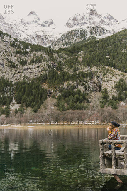 Side view of lady sitting on bench and looking at amazing view of water surface between high mountains with trees in snow and cloudy heaven in Pyrenees