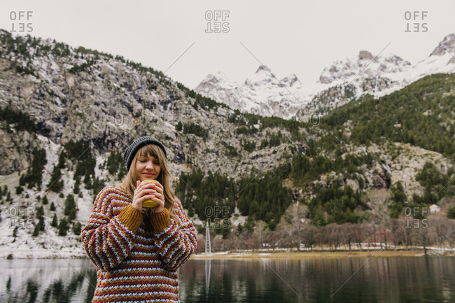 Young lady sitting on bench closed eyes near amazing view of water surface between high mountains with trees in snow in Pyrenees