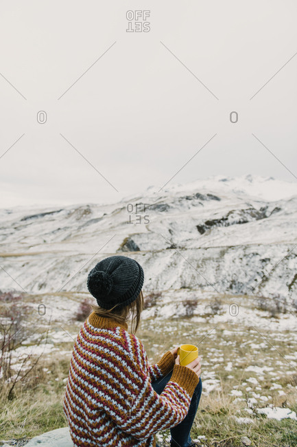 Back view of young lady in sweater and hat holding mug and looking at hills in snow in Pyrenees