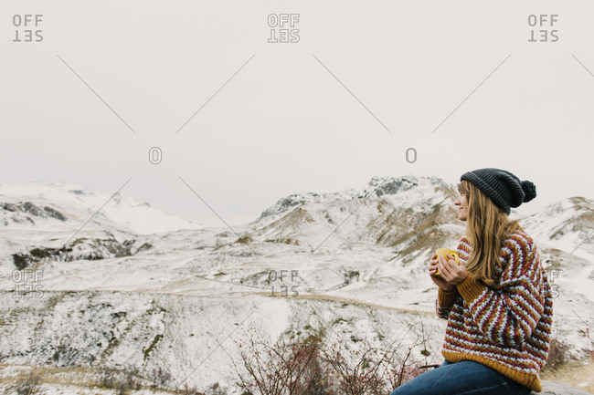 Side view of young lady in sweater and hat holding mug and looking at hills in snow in Pyrenees