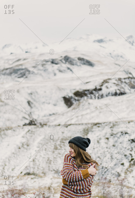 Attractive young lady in sweater and hat with crossed hands near hill on blurred background in Pyrenees