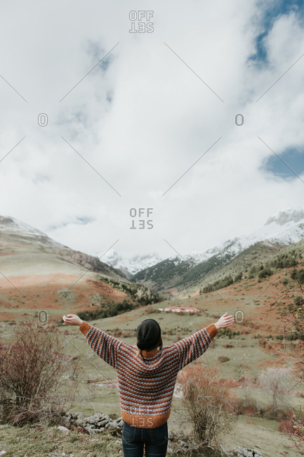 Back view of young lady in sweater and hat holding standing in a beautiful landscape between mountains with arms up in Pyrenees