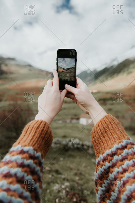 Crop hands of lady with mobile phone shooting picturesque view of valley with wonderful mountains and cloudy heaven in Pyrenees