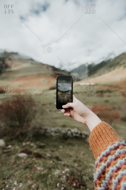Crop hand of lady with mobile phone shooting picturesque view of valley with wonderful mountains and cloudy heaven in Pyrenees