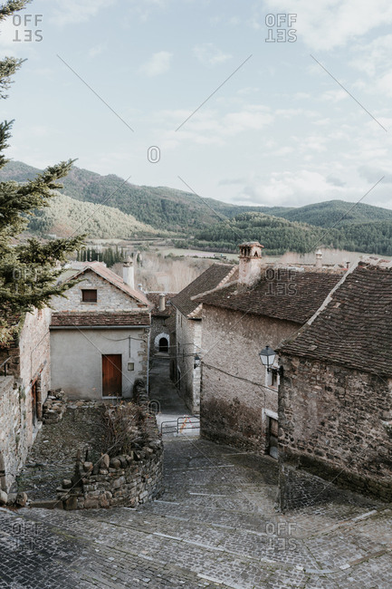 Panoramic view of ancient town near high hills with forest and blue sky with clouds in Pyrenees